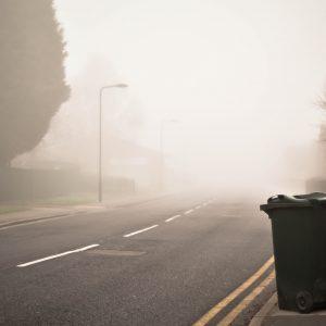 Mülltonne an nebeliger Straße